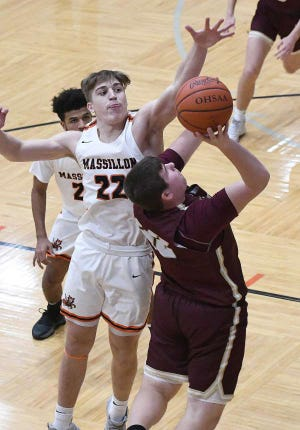 Massillon's Caiden Woullard goes for a block during a game last season against Stow. Woullard and the Tigers were finally able to get back on the basketball court for a regular-season game this past weekend against Ashland and University School.