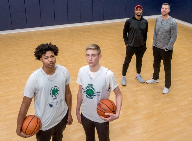 Lathan Sommerville, left, and Cooper Koch, both 15, are following in the footsteps of their famous fathers, Morton standout and former member of the New York Knicks J.R. Koch, far right, and Peoria Central and Bradley grad Marcellus Sommerville. The pair are playing for the Peoria Notre Dame Irish and often practice together at a friend's home court in Dunlap.