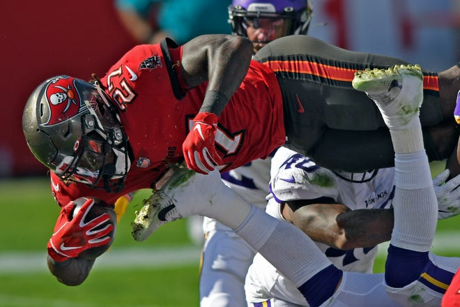 Tampa Bay running back Ronald Jones II (27) dives over the line to score on a 1-yard touchdown run against the Minnesota Vikings during the first half on Sunday in Tampa.