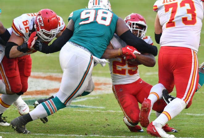 Miami Dolphins nose tackle Raekwon Davis (98) brings down Kansas City Chiefs running back Clyde Edwards-Helaire (25) in the fourth quarter at Hard Rock Stadium in Miami Gardens, December 13, 2020.