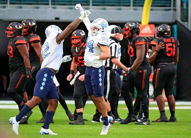 North Carolina Tar Heels linebackers Tomon Fox (12) and Jeremiah Gemmel (44) celebrate a stop in the second quarter at Hard Rock Stadium on Saturday.