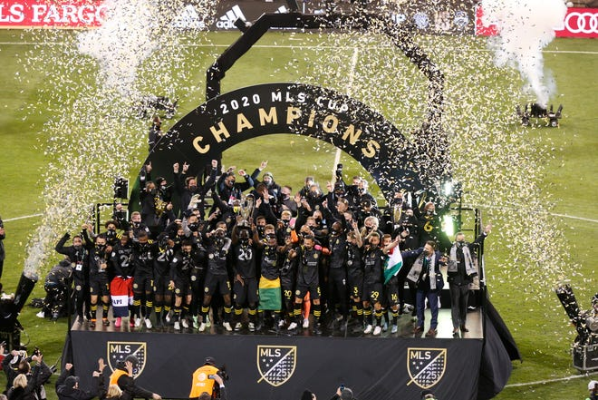Members of the Columbus Crew raise the cup after defeating the Seattle Sounders, 3-0, Saturday night in the MLS Cup championship game.