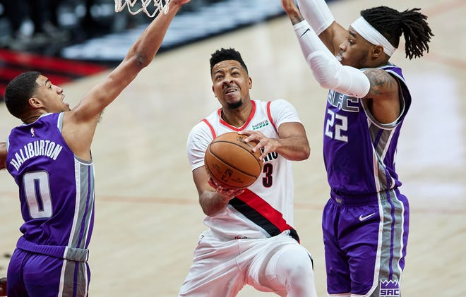 Portland's CJ McCollum, center, splits the defense of Sacramento's Tyrese Haliburton, left, and Richaun Holmes during the first half of Friday's game in Portland. The Trail Blazers' preseason continues Wednesday at Denver.