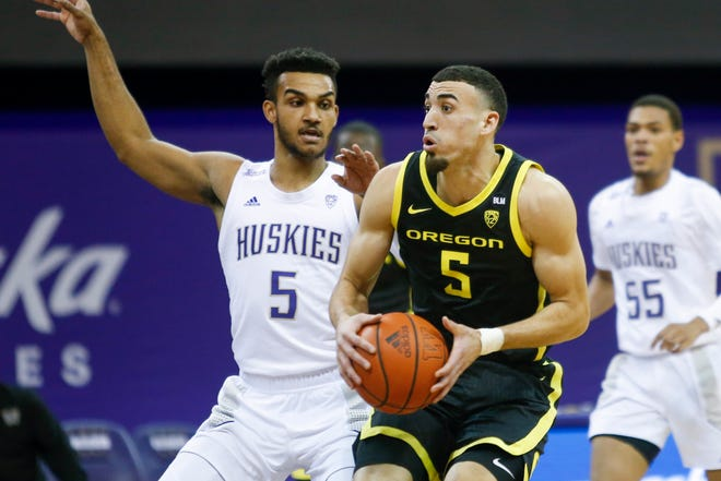 Oregon's Chris Duarte, who had 14 points and seven rebounds, tries to get past Washington's Jamal Bey during the Ducks' 74-71 win over the Huskies on Saturday at Alaska Airlines Arena.