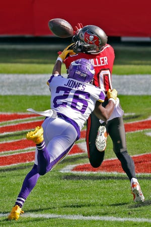 Tampa Bay Buccaneers wide receiver Scott Miller (10) pulls in a 48-yard touchdown pass from Tom Brady after getting in front of Minnesota Vikings defensive back Chris Jones (26) during the first half Sunday in Tampa. The Bucs won 26-14.
