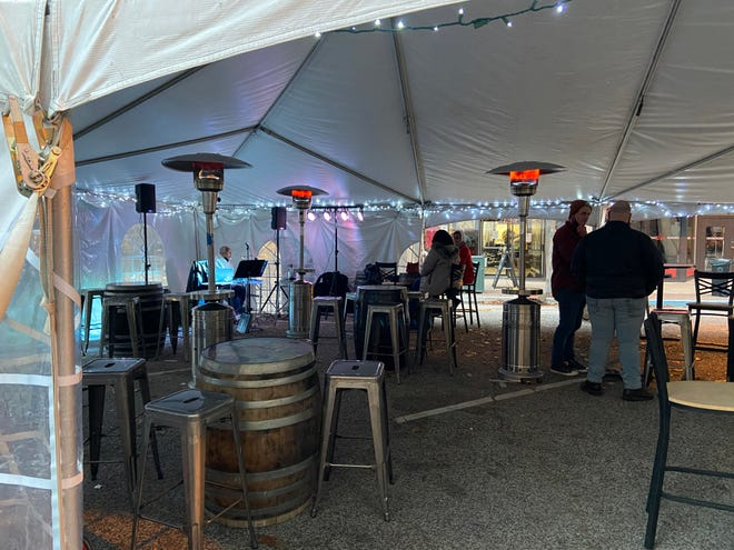 Patrons gather inside the heated tent that is shared by Buzz Bomb Brewing Company, Cafe Moxo and other businesses on Adams Street in downtown Springfield.