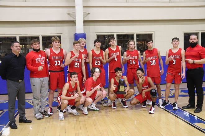 Members of the Prague Red Devils celebrate with their trophy after winning the championship Saturday of Bethel High School's First United Bank Classic at the B.E. Cantrell Fieldhouse.