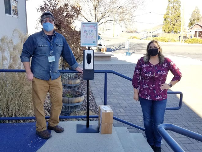 Forrest Lamb and Sabrina Ellin pose in front of the new sanitation station at Grenada Elementary on Wednesday