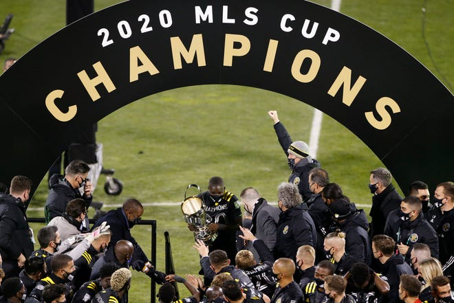 Columbus Crew's Jonathan Mensah, center, carries the trophy on stage after the Crew defeated the Seattle Sounders 3-0 in the MLS Cup championship game.