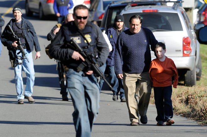 Parents leave a staging area after being reunited with their children following a shooting at the Sandy Hook Elementary School in Newtown, Conn., about 60 miles northeast of New York City, Dec. 14, 2012.