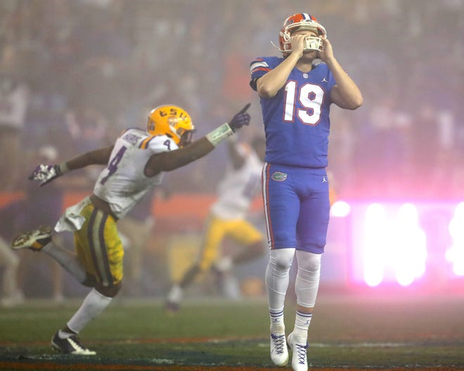 Florida kicker Evan McPherson hold his helmet in dejection Saturday night after missing a last-second field goal that would have tied the game against LSU at Ben Hill Griffin Stadium. Florida lost 37-34 to the Tigers.