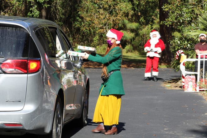 Autumn Fuchs, a 27-year-old Santa Fe College student, hands presents to foster families Sunday during the drive-thru Christmas for the Community parade. The University City Church of Christ partners with the Partnership for Strong Families each year to provide holiday presents for about 150 foster children. [Emily Mavrakis/The Gainesville Sun]