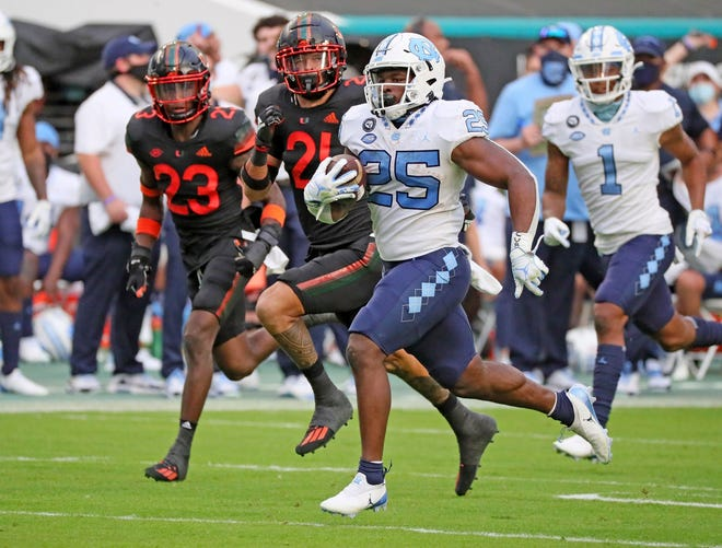 North Carolina running back Javonte Williams races through open space as Miami defenders Te'Cory Couch, back left, and Bubba Bolden give chase during Saturday's game at Hard Rock Stadium.