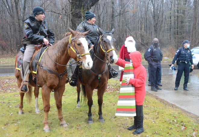 In a heavy rain and while holding one of his Christmas gifts, Jayden Treat pets the horse of Christine Moody, who with posse member Andrew Chantrenne and several police officers delivered presents Saturday for Shop With a Cop.