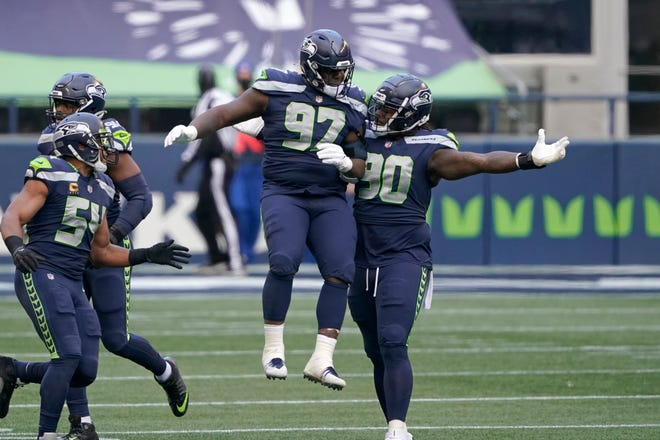Seattle Seahawks Jarran Reed (90) and Poona Ford (97) celebrate after the New York Jets missed a field goal during the first half Sunday.