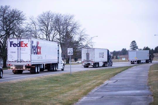UPS, FedEx and Boyle trucks carrying Covid-19 vaccine leaving at Pfizer Global Supply in Portage, Mich., Sunday, Dec. 13, 2020.