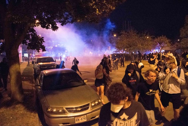 A crowd disperses as police deploy tear gas during a protest in downtown Madison, Wis., on Aug. 24, 2020. The protest came in response to the police shooting of Jacob Blake in Kenosha, Wis., one day earlier.