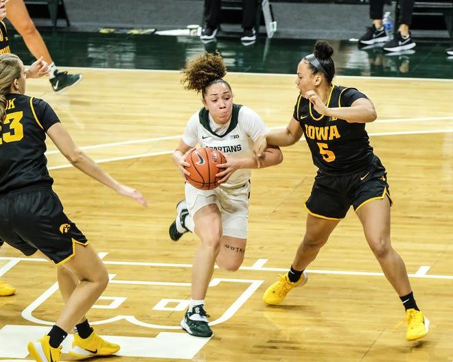 MSU's Alyza Winston (3)  moves around Iowa's Alexis Sevillian (5) at the Breslin Center Saturday, Dec. 12, 2020. MSU held on to win 86-82.