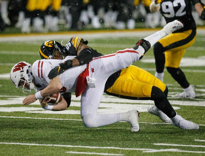 UW quarterback Graham Mertz is sacked by Iowa's Chauncey Golston in the third quarter.