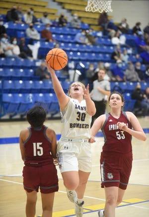 Mountain Home's Addison Yates splits two Springdale defenders earlier this season at The Hangar. The Lady Bombers fell 52-23 at Cabot on Saturday.
