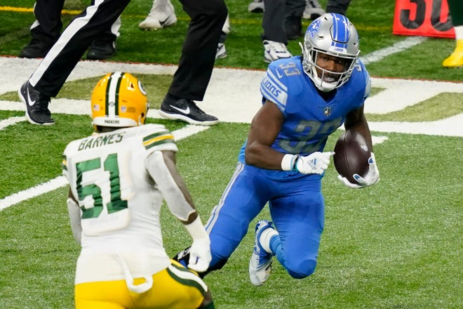 Detroit Lions running back Kerryon Johnson (33) runs by Green Bay Packers inside linebacker Krys Barnes (51) during the first half of an NFL football game, Sunday, Dec. 13, 2020, in Detroit.