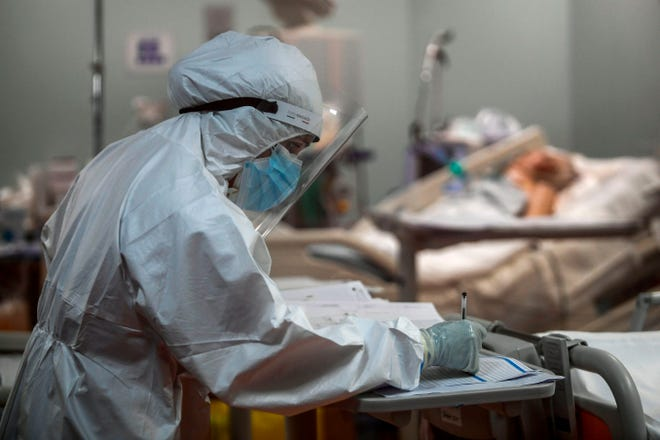 A nurse and patient in an intensive care unit treating a COVID-19 patient.