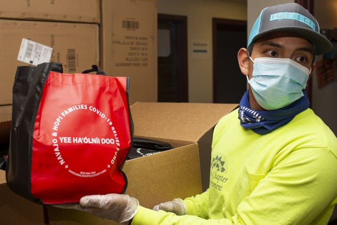 Colin Tsosie, a lead with AmeriCorps, shows off a kit containing masks, sanitizer and wipes at the Chinle Chapter Government house that will be distributed to members of the Chinle Chapter in Chinle, Ariz. on the Navajo Nation on Dec. 9, 2020.