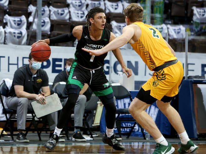 SIOUX FALLS, SD - DECEMBER 12: Seybian Sims #1 of the North Dakota Fighting Hawks looks over the defense while being guarded by Jaxon Knotek #2 of the North Dakota State Bison during the CU Mortgage Direct Dakota Showcase at the Sanford Pentagon on December 12, 2020 in Sioux Falls, South Dakota.