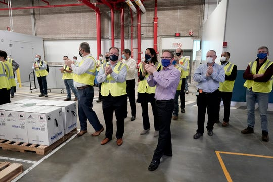 Pfizer employees clap after line workers finished packing boxes containing the Pfizer-BioNTech COVID-19 vaccine to be shipped around the country.