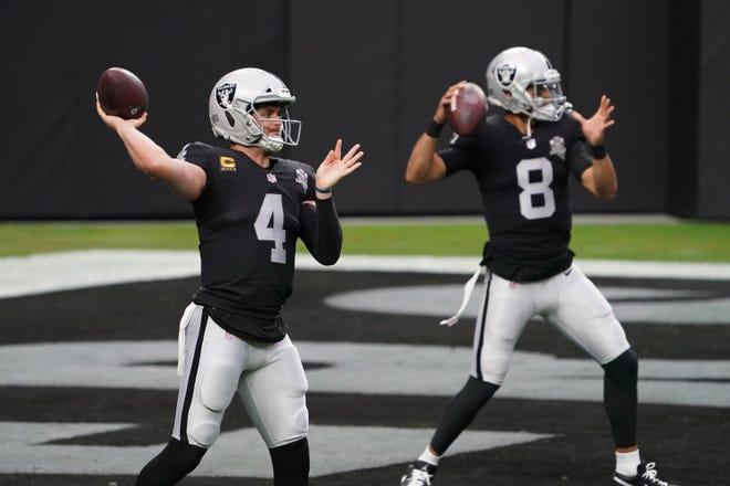 Las Vegas Raiders quarterback Derek Carr (4) and quarterback Marcus Mariota (8) warm up before the game against the Indianapolis Colts at Allegiant Stadium.