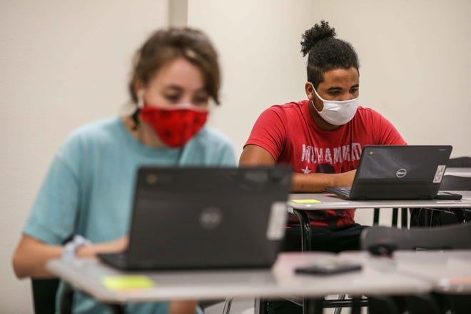 Akaris Smith and Mikaela Kuentz attend in person classes wearing masks at Lake Travis High School on Sept. 16. Superintendent Paul Norton said about 60% of students will conclude the fall semester onsite, with more expected to return to in-person learning in January.