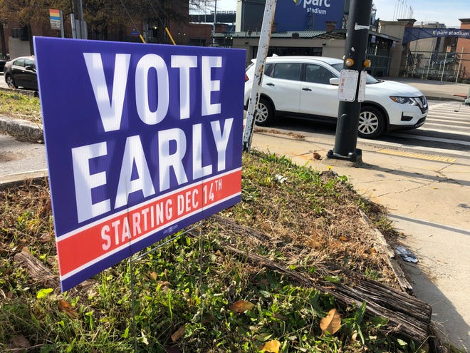 A sign in an Atlanta neighborhood on Friday, Dec. 11, 2020, urges people to vote early in Georgia's two U.S. Senate races. (AP Photo/Jeff Amy)