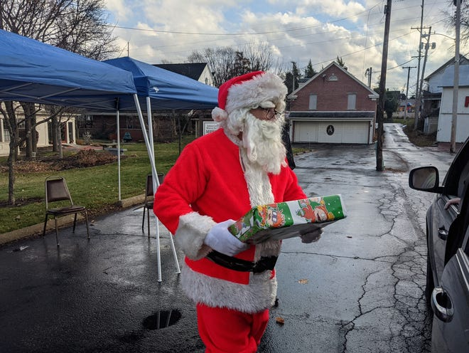 Santa gives a foster child a gift Saturday during the Ashland Elks drive-thru Foster Kids Christmas by the Lodge event.