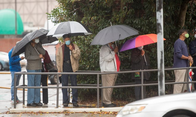 People wait in line on the first day of advance voting for Georgia's Senate runoff election at the Bell Auditorium in Augusta, Ga., Monday morning, December 14, 2020.