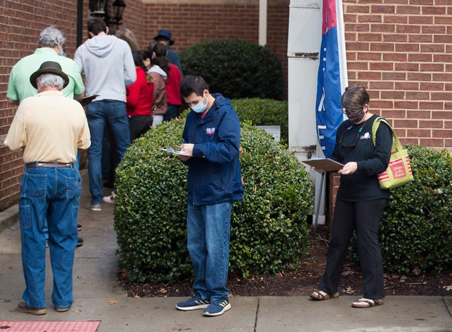 People wait in line Monday to vote in Georgia's Senate runoff elections at the Columbia County Government Complex in Evans. Interest is high in the runoffs and many have voted early.