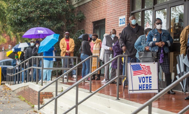 People wait in line Monday on the first day of advance voting for Georgia's Senate runoff election at Bell Auditorium.