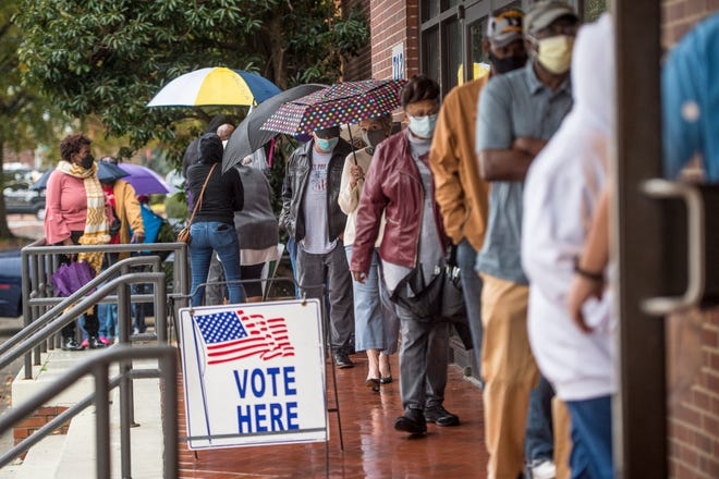 People wait in line on the first day of advance voting for Georgia's Senate runoff election at the Bell Auditorium in Augusta Monday.