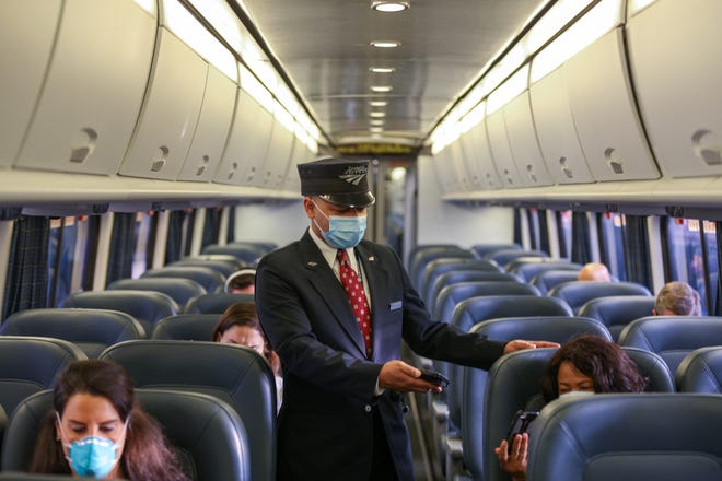 An Amtrak conductor checks a passenger's ticket. Apple Pay, Google Pay and PayPal are now available when checking out on theAmtrakmobile app and website.
