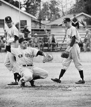 New York Yankees catcher Yogi Berra, troubled with a skin infection, wears white gloves to protect his hands as he warms up a pitcher during spring training in St. Petersburg, Fla. Walking behind Yogi are outfielder John Reed and infielder Phil Linz, right.