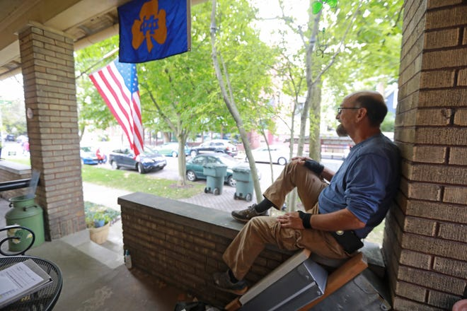 From his favorite perch on his German Village home, Jamie Weilbacher waves to friend Mary Zacks. Weilbacher can trace his roots back to some of the original German residents of the neighborhood.