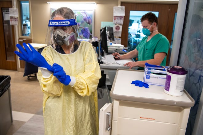 Respiratory therapist Brenda Clingerman puts on personal protective equipment before entering a patient's room during her shift inside the Mount Carmel Grove City Hospital COVID-19 ward.