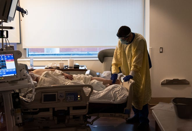 ICU nurse Kyle Day tends to a 25-year-old patient inside the COVID-19 ward of Mount Carmel Grove City Hospital on Wednesday. She is one of two patients under Day's care during his shift. The current ratio for nurses in the Grove City ICU is 2 to 1, but there have been times during the pandemic when that patient-to-nurse ratio has reached 3 to 1.