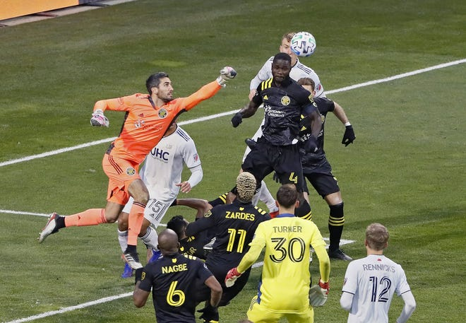 Goalkeeper Andrew Tarbell punches the ball out of harm's way late in the MLS Eastern Conference final against New England on Dec. 6.