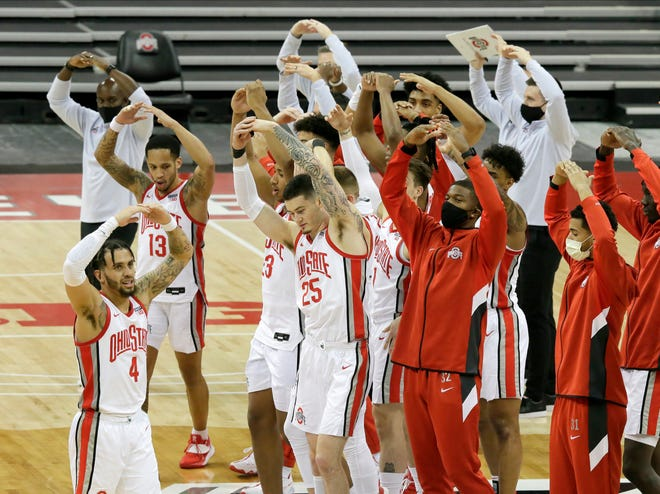 """The Ohio State Buckeyes sing """"Carmen Ohio"""" to an empty arena following Sunday's NCAA Division I basketball game against Cleveland State Vikings at Value City Arena in Columbus, Oh. on December 13, 2020. Ohio State won the game 67-61."""