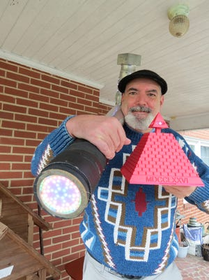 Joel Leonard is spearheading a worldwide time capsule program, Bury 2020. Here, he holds a 50-pound hammer that has more than 1000 LED lights on it that was made at several different makerspaces. The pyramid lights up and shows the eye on a dollar bill. He says the eye reminds us of how we were economically devastated by Covid-19 and the debates on Capitol Hill.