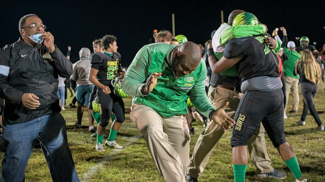 Lake Minneola head coach Walter Banks is overcome with emotion after the Hawks beat St. Augustine 49-48 in triple overtime in Friday's Class 6A state semifinals at the Hawks Nest in Minneola. Lake Minneola will play Miami Central Friday in Tallahassee for the Class 6A state championship. [PAUL RYAN / CORRESPONDENT]