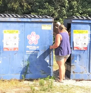 A customer uses a Republic Services recycling bin last summer. Republic has been retained as the county recycling service.