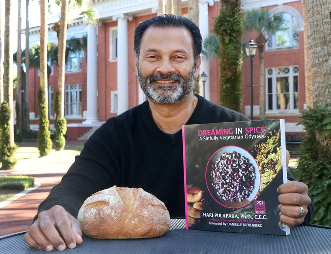 "Chef and Stetson University professor Hari Pulapaka with his new cookbook, ""Dreaming in Spice: A Sinfully Vegetarian Odyssey,"" and a fresh loaf of No-Knead Covid-19 Table Bread from a recipe in the book."