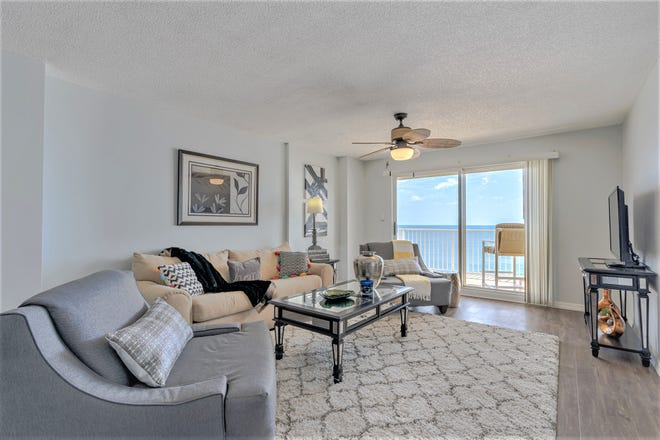 The great room of this this immaculate, two-bedroom, two-bath, move-in-ready condominium home opens to the oceanfront balcony.