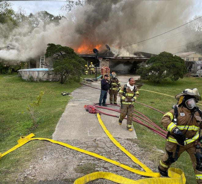 Firefighters work to extinguish a house fire in Darrow Dec. 5.